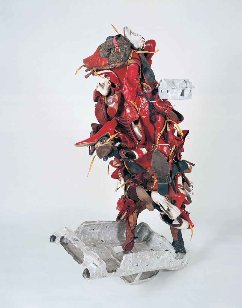 """Little moved to Oklahoma in 1980. There he taught sculpture and began a series of shoe works that would take him away from ceramics.  """"Burn"""" (1985) is an example of one of these shoe works with the incorporation of paper shell forms (an upside down Corvette) made of dictionary pages and a small house over his left shoulder made from the pages of the book of Exodus from the Old Testament. """"Burn"""" was actually made in New York, where Little lived from1985 to 1986; Mixed Media, Shoes, leather, other clothing, paint, dictionary and Bible pages over steel and paper frame; 72"""
