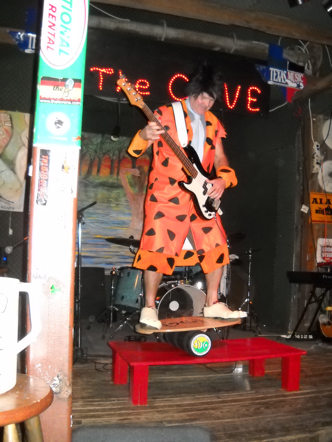 Gary Sweeney as Fred Flintstone on a bogey board (playing bass to a Kurt Cobain song)