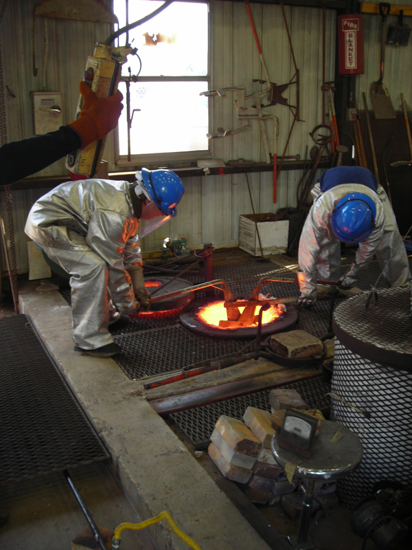 Reaching in to retrieve the crucible from the melting furnace